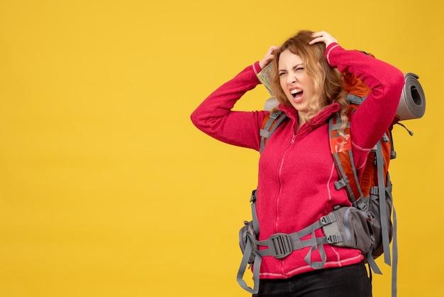 Vista dall'alto di giovane ragazza in viaggio nervoso in mascherina medica raccogliendo i suoi bagagli e tenendo la mappa