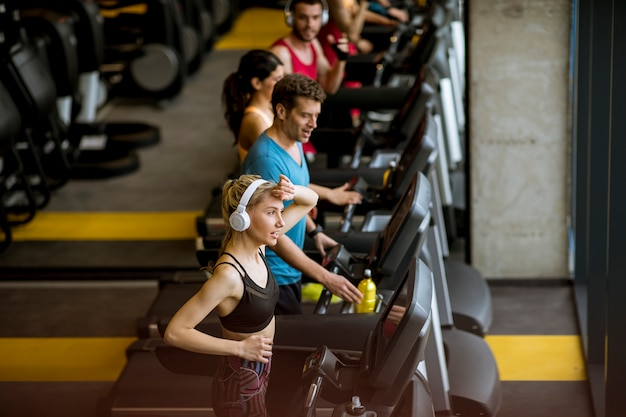 Top view at young people running on treadmills in modern gym
