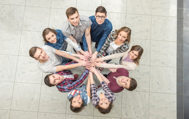 Top view of young people with their hands together.