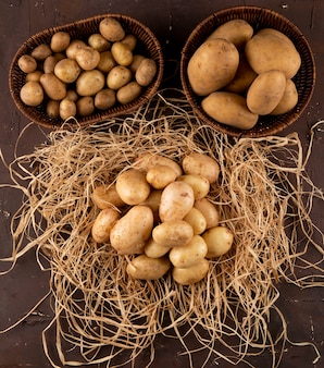 Top view young potatoes on hay with potatoes in baskets