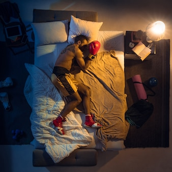 Top view of young professional boxer, fighter sleeping at his bedroom in sportwear with gloves