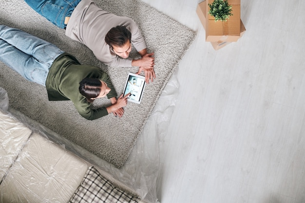 Top view of young restful couple lying on carpet and scrolling through online adverts of new real estate in touchpad