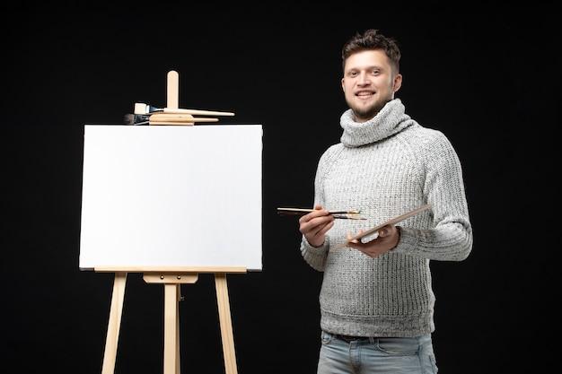 Vista dall'alto del giovane pittore maschio soddisfatto su nero isolato