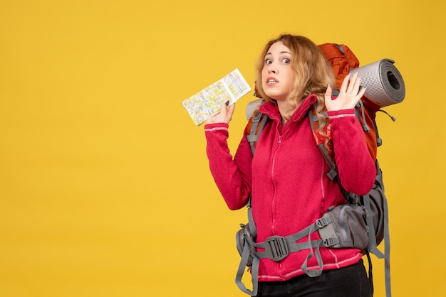 Vista dall'alto di giovane ragazza in viaggio spaventata in maschera medica raccogliendo i suoi bagagli e tenendo la mappa