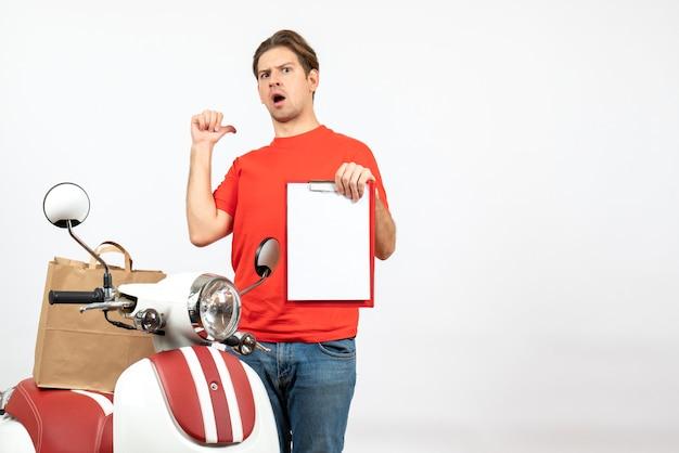 Vista dall'alto del giovane ragazzo delle consegne scioccato in uniforme rossa in piedi vicino allo scooter che mostra il documento che punta indietro sul muro bianco