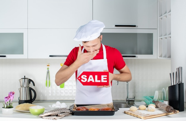 Top view of young sleepy male chef showing sale sign in the white kitchen