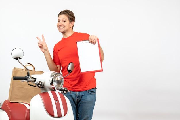 Vista dall'alto di giovane ragazzo di consegna sorridente in uniforme rossa in piedi vicino a scooter che mostra documento che fa gesto di vittoria sul muro bianco