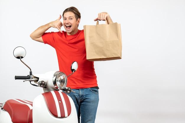 Vista dall'alto di giovane ragazzo di consegna sorridente in uniforme rossa in piedi vicino a scooter che mostra il sacchetto di carta facendo mi chiama gesto sul muro bianco