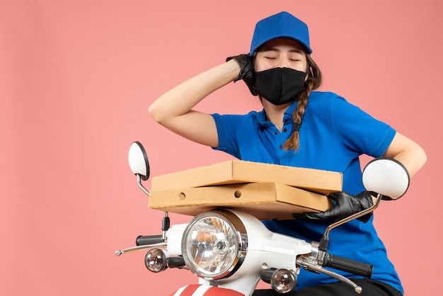 Top view of young smiling female courier wearing medical mask and gloves holding boxes on pastel peach