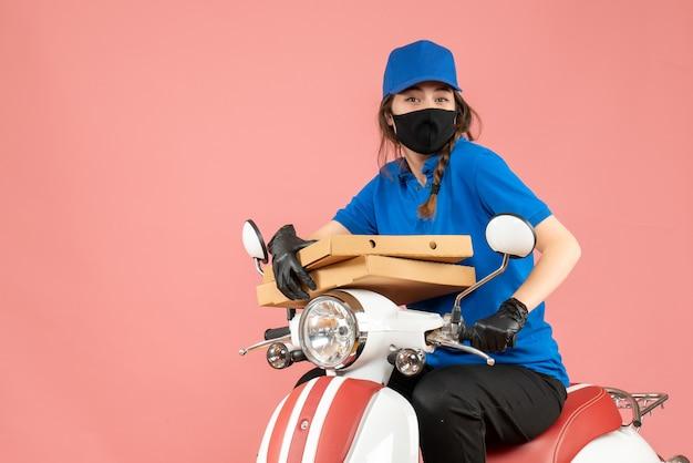 Vista dall'alto del giovane corriere femminile sorridente che indossa maschera medica e guanti seduto su uno scooter che consegna ordini su pesca pastello