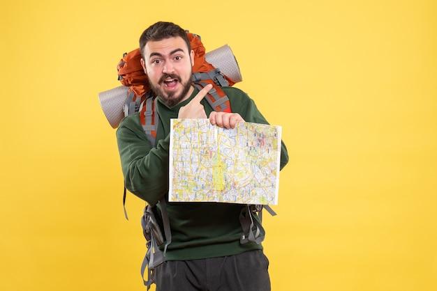 Vista dall'alto di un giovane ragazzo in viaggio sorridente con uno zaino che tiene in mano una mappa e punta verso l'alto sul giallo