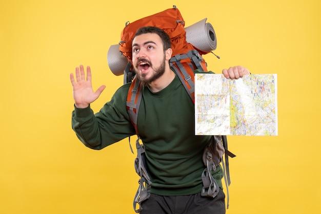 Vista dall'alto di un giovane ragazzo in viaggio sorridente con uno zaino che tiene in mano una mappa e mostra cinque su giallo