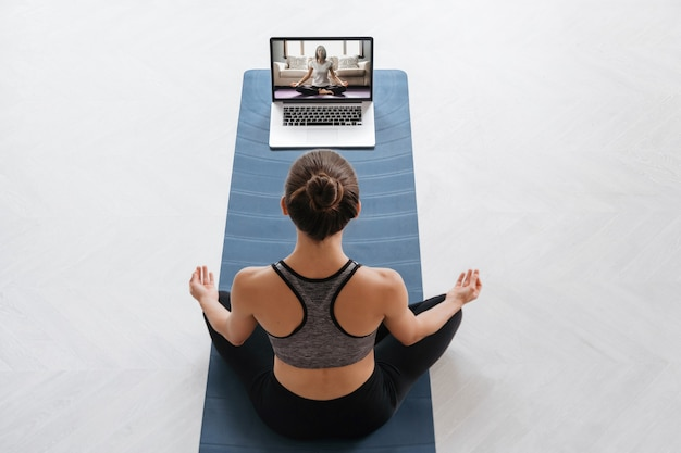Top view young sporty woman using laptop for training hatha yoga with virtual instructor, doing sukhasana