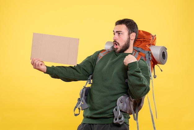 Top view of young surprised and emotional travelling guy with backpack holding a sheet without writing on yellow