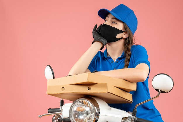 Vista dall'alto di una giovane donna pensante che indossa una maschera medica e guanti che tengono scatole su una pesca pastello