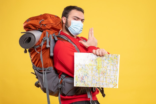 Top view of young thinking traveller guy wearing medical mask with backpack holding map pointing up on yellow