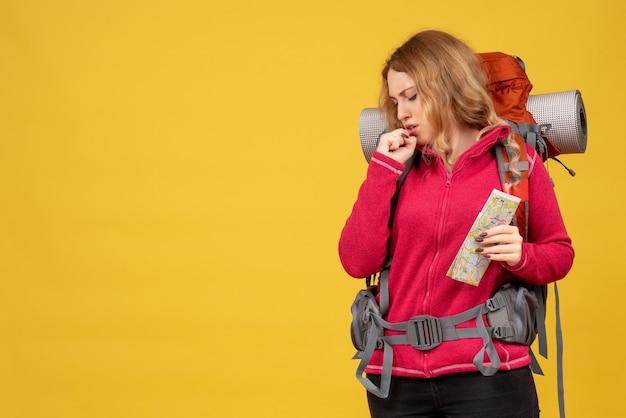 Vista dall'alto di giovane ragazza stanca in viaggio in mascherina medica raccogliendo i suoi bagagli e tenendo la mappa