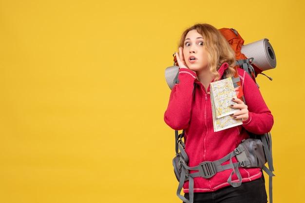 Vista dall'alto della giovane ragazza in viaggio in mascherina medica raccogliendo i suoi bagagli e tenendo la mappa ascoltando gli ultimi pettegolezzi