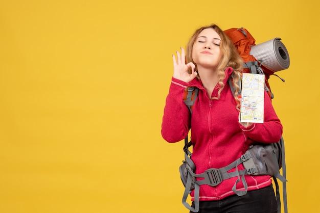 Vista dall'alto di giovane ragazza in viaggio in mascherina medica raccogliendo i suoi bagagli e tenendo la mappa facendo gesto di occhiali