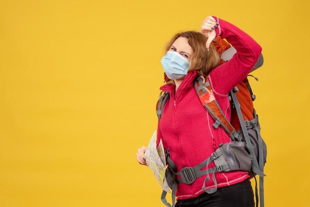 Vista dall'alto della giovane ragazza in viaggio in mascherina medica raccogliendo i suoi bagagli e facendo un cattivo gesto
