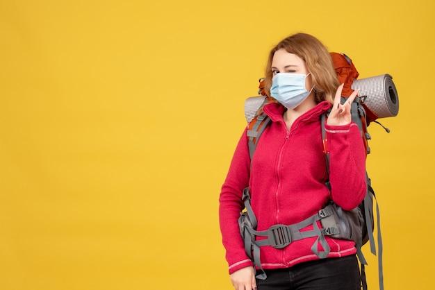 Vista dall'alto della giovane ragazza in viaggio in mascherina medica raccogliendo i suoi bagagli e facendo il gesto di vittoria