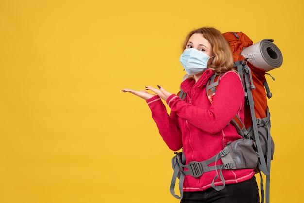 Vista dall'alto della giovane ragazza in viaggio in mascherina medica raccogliendo i suoi bagagli e indicando qualcosa sul lato destro