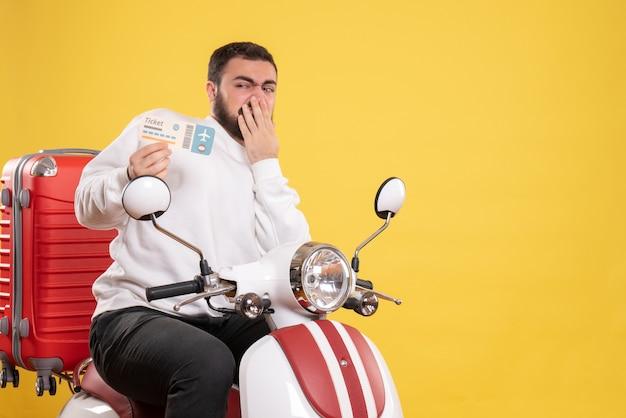 Vista dall'alto di un giovane viaggiatore incerto e incerto seduto su una motocicletta con la valigia sopra che tiene il biglietto giallo