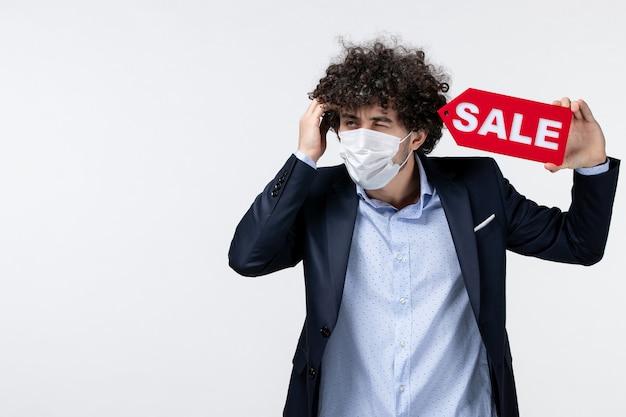 Vista dall'alto di un giovane uomo d'affari incerto e incerto in tuta e che indossa la sua maschera che mostra l'iscrizione di vendita in posa per la fotocamera