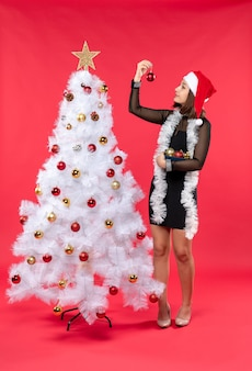 Top view of young woman in a black dress with santa claus hat and decorating christmas tree on red