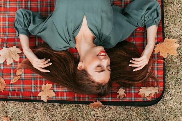 ピクニック毛布で秋を楽しむ平面図若い女性