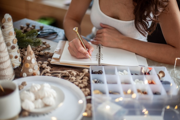 Top view of young woman is writing goals for new year 2021 on diary on desk with handcrafted christmas tree decorations, stars, buttons and tea with marshmallow. concept of planning new goals.
