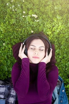 Top view of young woman listening to music.