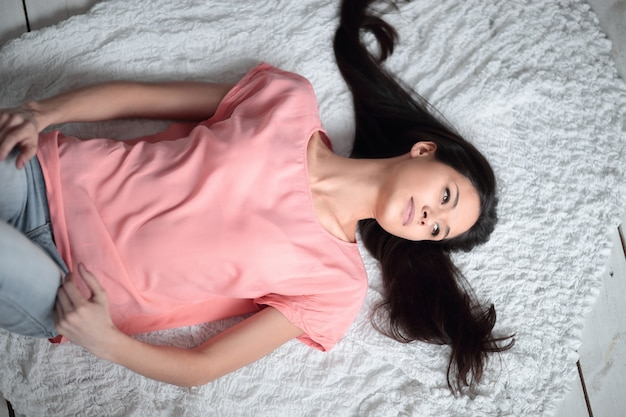 Top view.young woman lying on white carpet in living room.