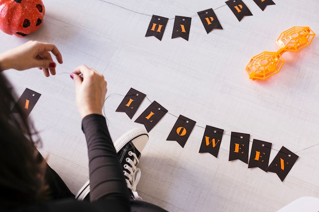 Top view of a young woman makes halloween garland.creative diy . home decor project party.halloween crafts inspiration.