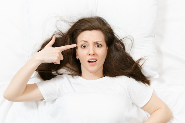 Top view young woman point fingers to head as if she about shoot herself, lying in bed with white sheet, pillow, blanket