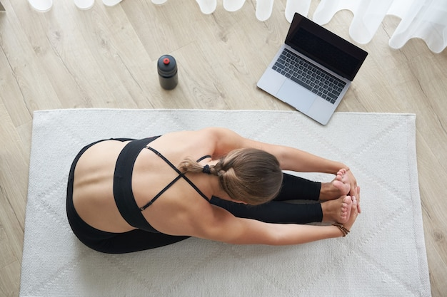 Top view of young woman practicing yoga sitting in seated forward bend exercise paschimottanasana