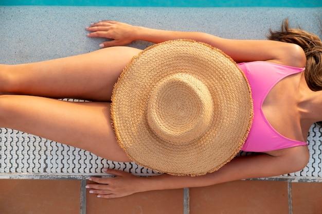 プールのそばでリラックスしてトップビューの若い女性
