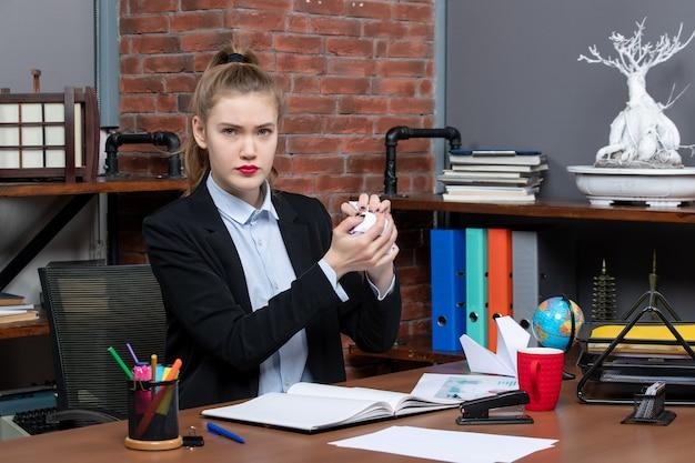Vista dall'alto di una giovane donna seduta a un tavolo e in possesso di carta avvolta in ufficio