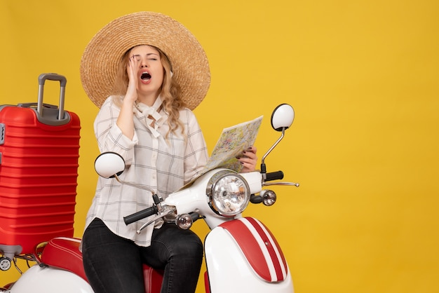 Top view of young woman wearing hat and sitting on motorcycle and holding map calling someone on yellow