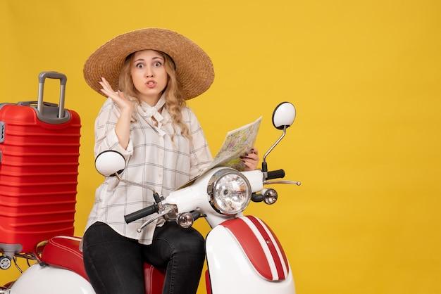 Vista dall'alto della giovane donna che indossa un cappello e seduto sulla moto e tenendo la mappa confusa sul giallo