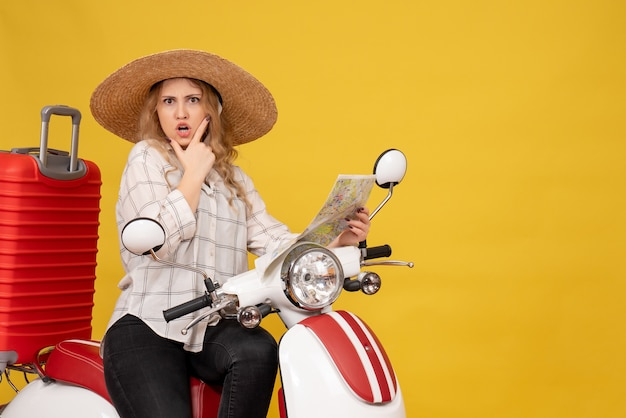 Top view of young woman wearing hat and sitting on motorcycle and holding map with confused facial epression on yellow
