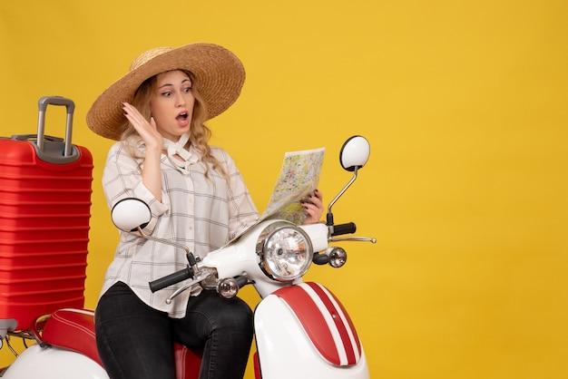 Vista dall'alto della giovane donna che indossa un cappello e seduto sulla moto e guardando la mappa con sorprendente epressione facciale su giallo