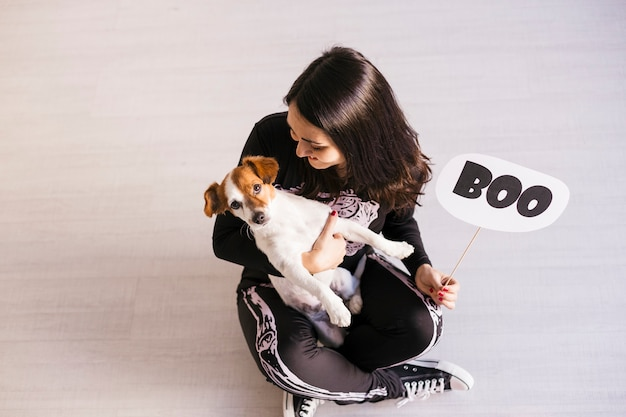 Top view of a young woman with her cute small dog wearing getting ready for halloween. woman wearing a skeleton costume. halloween concept. indoors