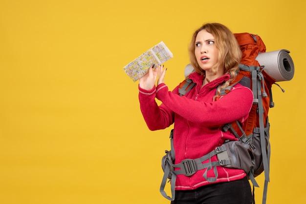 Vista dall'alto della giovane ragazza in viaggio chiedendo in maschera medica raccogliendo i suoi bagagli e tenendo la mappa
