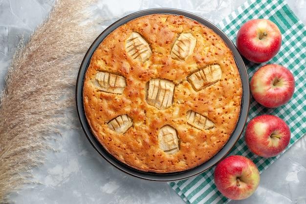 上面図白い机の上に赤いリンゴと鍋の中で甘い焼きたておいしいアップルパイ