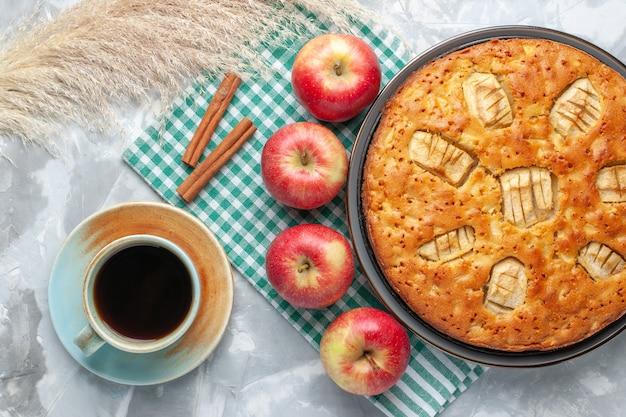 Vista dall'alto yummy torta di mele dolce al forno all'interno della padella con tè e mele sulla scrivania bianca