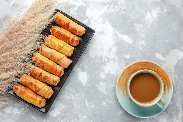 明るい背景の上のミルクコーヒーとおいしい腕輪の上面図ペストリークッキングケーキ甘い砂糖