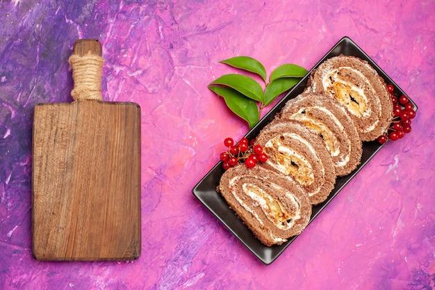 Вид сверху вкусные бисквитные рулеты с ягодами на розовом фоне