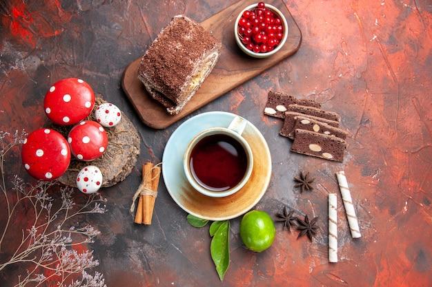 Vista dall'alto gustoso biscotto rotoli con una tazza di tè su sfondo scuro