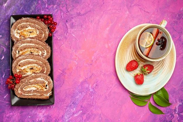 Vista dall'alto gustoso biscotto rotoli con una tazza di tè sulla scrivania rosa